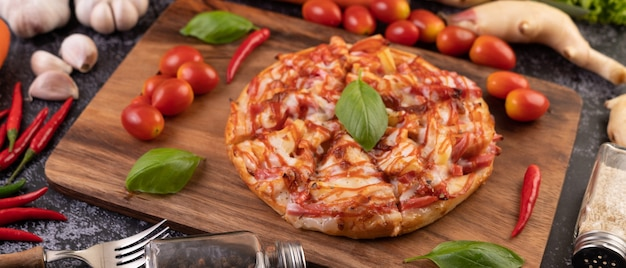 Pizza in a wooden tray with tomatoes chili and basil.