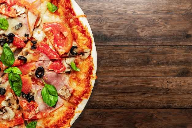 Pizza on wooden with ham, olives, tomatoes and green basil