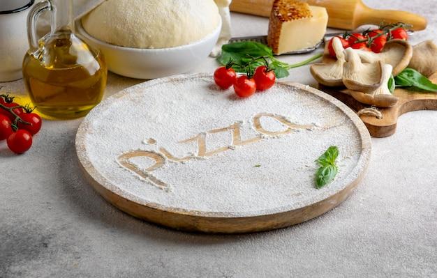 나무 보드에 밀가루로 작성 된 피자 단어