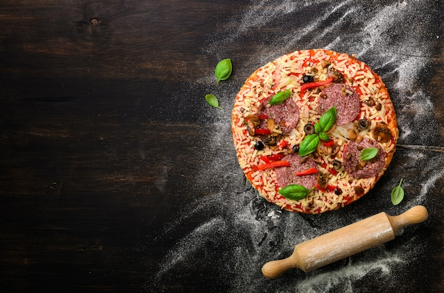 Pizza woth basil, rolling pin, flour on dark black background, copy space, top view