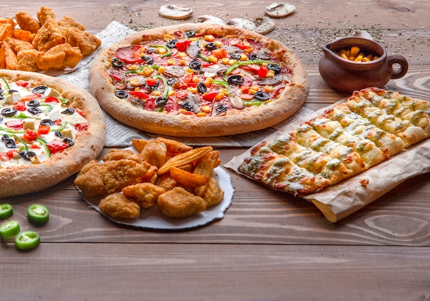 Pizzas, chicken bbq, fried potatoes and cheese rolls on the wooden table