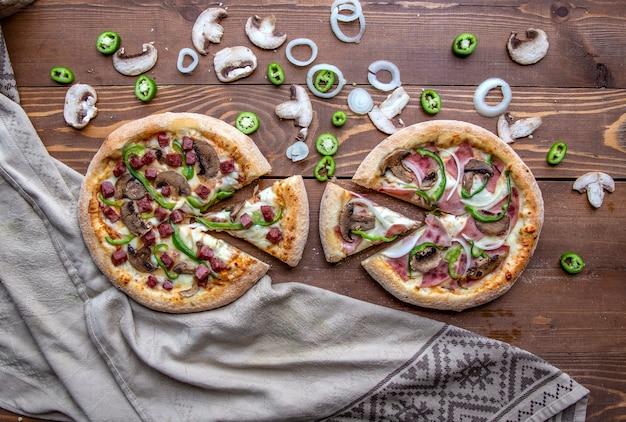 Пицца с нарезанными колбасками, мясом, луком, грибами и зеленым перцем