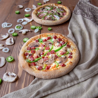 Pizzas with chopped sausages, meat, onions, mushrooms and green pepper