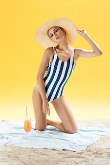 麦わら帽子とメガネで太陽から隠れているビーチで夏の日に不健康な日光浴をしている日焼けした若い女性。トレンディなメイクアップのスモーキーアイ。バナナとplのスムージーやオレンジジュースを飲む