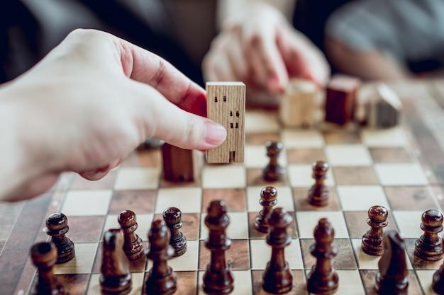 ビジネスマン移動の手チェスゲーム、競争の成功plの建物と家のモデル