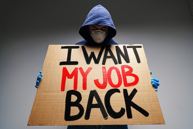 Placard 'i want my job back' in hands of protester man wearing mask