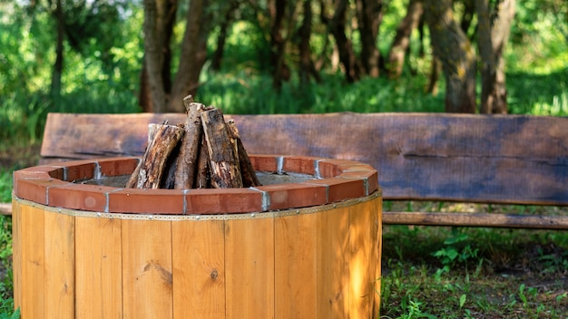 Place for campfire with wooden bench at glamping. greenery around