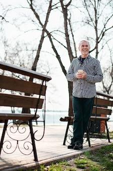 Место для музыки. низкий угол рефлексивного пожилого человека, стоящего в парке и слушающего музыку