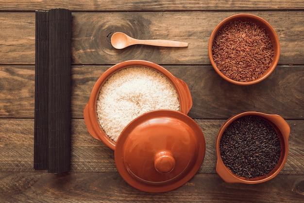 나무 테이블에 다른 그릇에 생 쌀된 쌀과 매트를 놓으십시오
