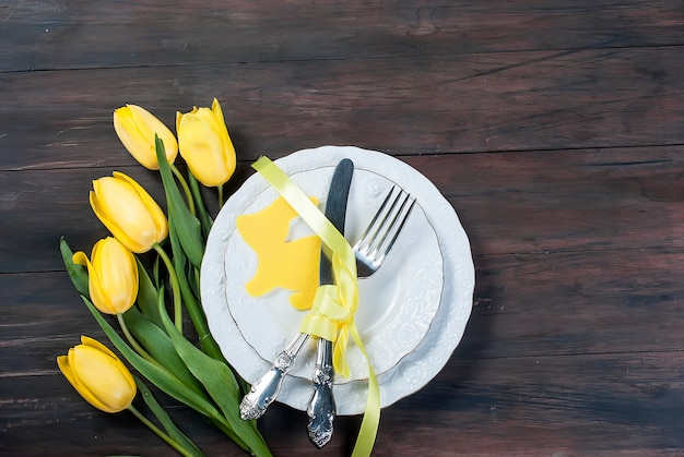 Place setting for easter on a wooden background