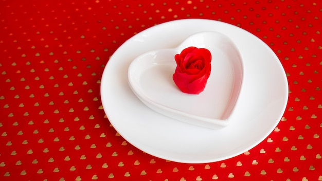 Place setting in red and white - for valentine or other event. white plate in the shape of a heart with a decor of roses on a red