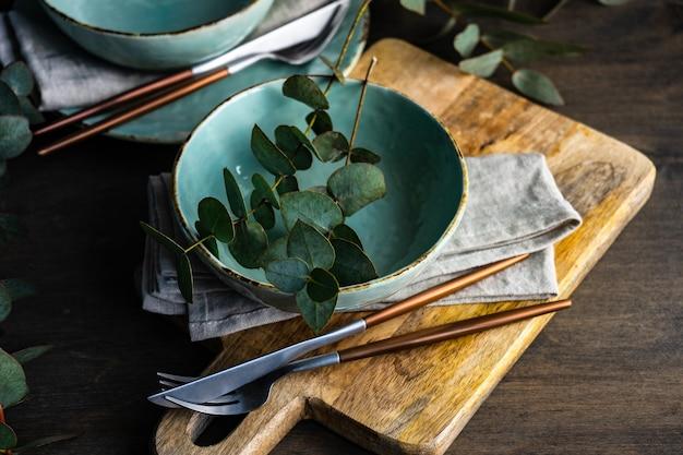 나무 테이블에 신선한 유칼립투스 잎으로 장소 설정