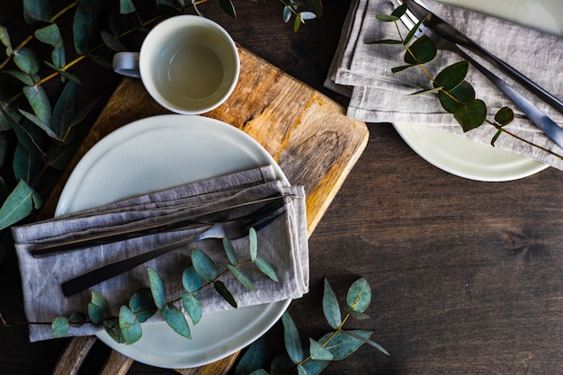 Place setting with fresh eucalyptus leaves on wooden table