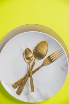 黄色の壁に分離されたプレート、ナイフ、フォークの場所の設定。ヴィンテージゴールドナイフ、フォーク、スプーン、プレート。ディナーの場所の設定。コピースペース