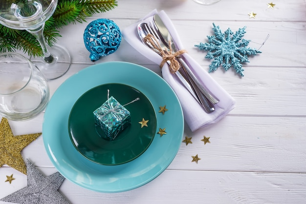 Place table setting for christmas white table with blue decor elements with green branches christmas tree