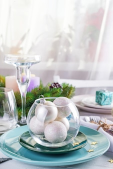 Place table setting for christmas white table with blue and silver decor elements with green branches christmas tree