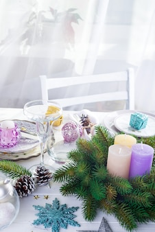 Place table setting for christmas white table with purple decor elements and green wreath christmas tree
