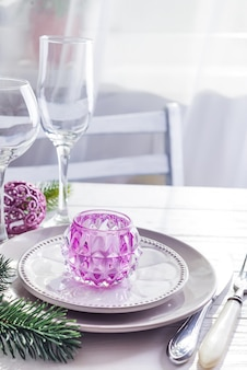Place table setting for christmas white table with purple decor elements with green branches christmas tree
