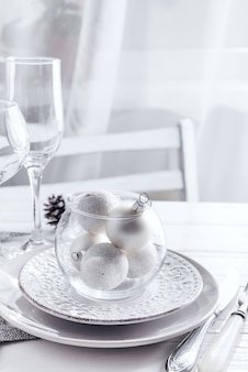 Place table setting on white table with christmas decor elements. silver color