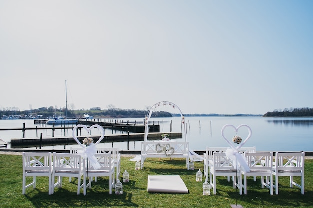 Place venue for the wedding ceremony by the sea. white chairs and solemn arch