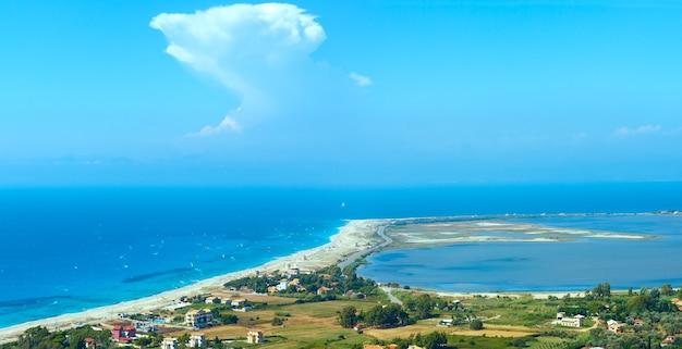 Место, где соединяются небо, море и горизонт горы. красивый летний пляж на побережье лефкады и кайтбордеры (греция, ионическое море, вид сверху). все люди не идентифицируются.