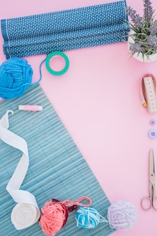 Placemat; ribbon; scissor; spool; measuring tape; button and wool on pink background