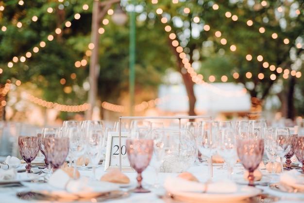 Расстановка столов со стаканами, столовыми приборами, тарелками на свадьбе на открытом воздухе