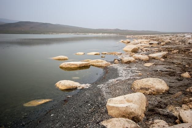 Россыпи крупных камней на берегу высыхающего озера среди холмов. туман. серое небо. тонировка.
