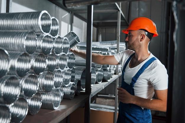 Размещение в правильном порядке. мужчина в военной форме работает на производстве. современные промышленные технологии.