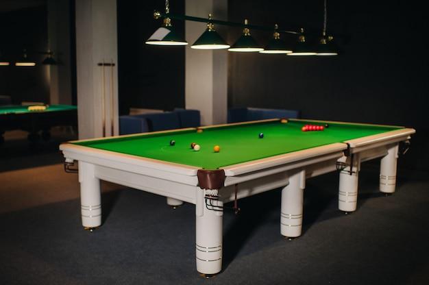 Placing snooker balls on a green billiard table.