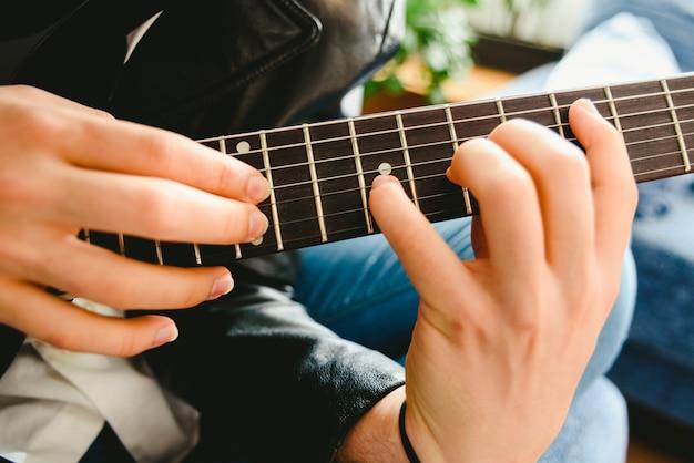 ギターに指を当てて、プロのギタリストがノートを演奏します。