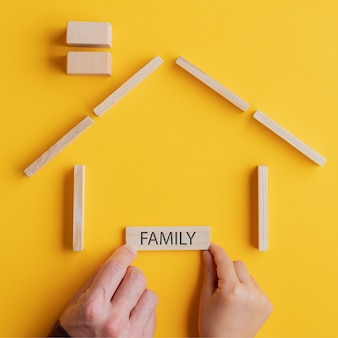 Placing a wooden peg with family sign on it in a house made of wooden blocks