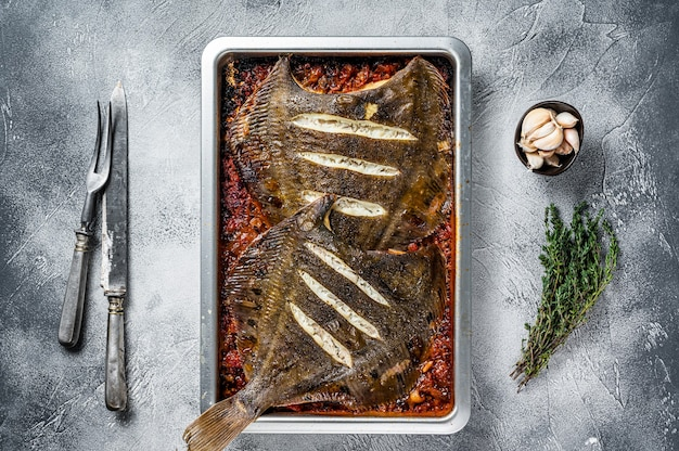 Plaice or flounder flat fish baked in a tomato sauce in baking tray. white background. top view.