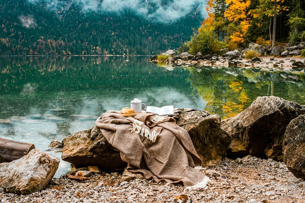 Plaid, croissant, book, cacao, with marshmallow near lake in bavarian alps, germany
