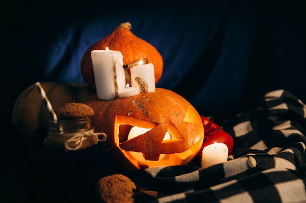 Plaid lies around halloween pumpking with shiny candles around it and a cup of hot chocolate with cookies