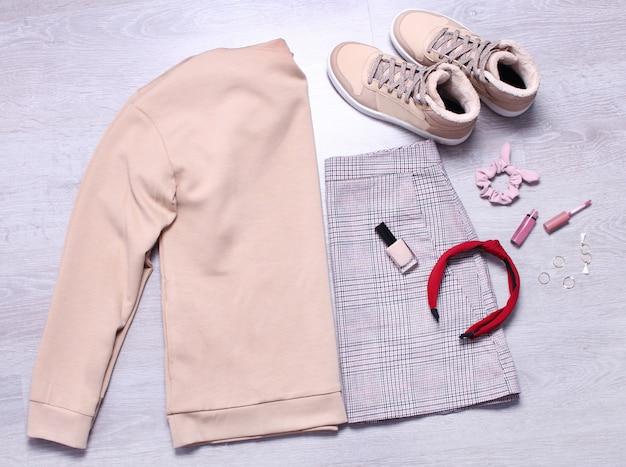 Plaid skirt, beige sweatshirt,beige sneakers, nail polish, lip gloss and accessories