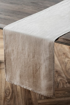 Plain beige table runner on a wooden table