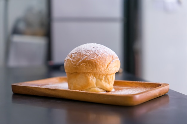 Plain butter bread with icing sugar powder on wooden plate