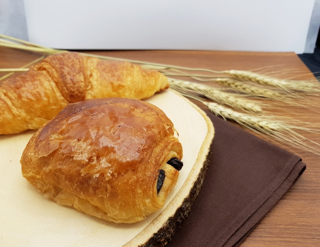 Plain and chocolate croissant on wooden board, rustic background