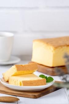 재료가 있는 나무 쟁반 배경 테이블에 있는 평범한 고전적인 대만 전통 스폰지 케이크(대만 카스텔라 카수테라)가 닫혀 있습니다.