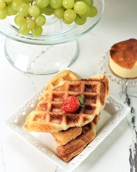 하얀 접시에 플레인 크리스피 크로플 크루아상 와플, 대리석 화이트 테이블 위에 딸기, 배경에 청포도. 한국에서 인기 있는 이 스낵
