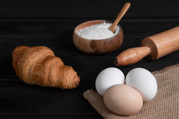 Plain croissants, bowl of flour and raw eggs on dark wooden surface. high quality photo