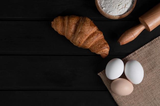 Croissant semplici, ciotola di farina, mattarello e uova crude su una superficie di legno scuro. foto di alta qualità