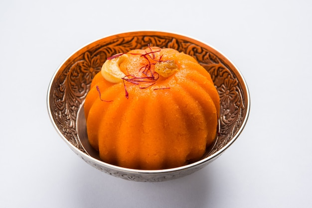 Plain or saffron flavoured semolina or soji halwa also known as sweet rava sheera or shira - indian festival sweet garnished with dry fruits. served in a plate or bowl, selective focus