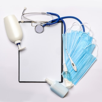 Plain table, stethoscope, bottle of lotion, sanitizer or liquid soap, protective mask and thermometer over light grey background