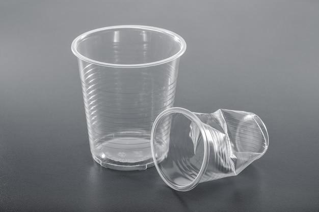 灰色のスペースに真っ白な真新しいしわくちゃのプラスチックカップ、クローズアップ。