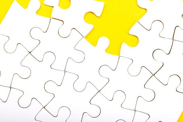 노란색 배경에 일반 흰색 직소 퍼즐.
