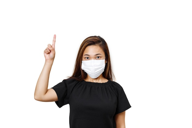 Plain white wall asian lady with one hand finger pointing upward for text space half body view of lady in black shirt lady looking straight wearing face mask to avoid spreading of coronavirus