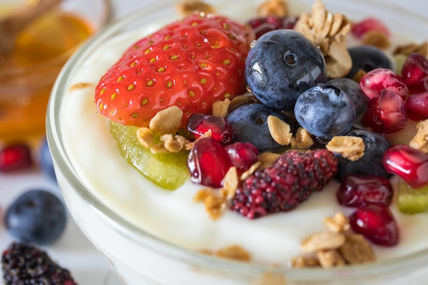 Plain yogurt with strawberry, blueberries, kiwi, granola, pomegranate in a glass bowl and honey on white wooden texture, healthy food and plant-based food