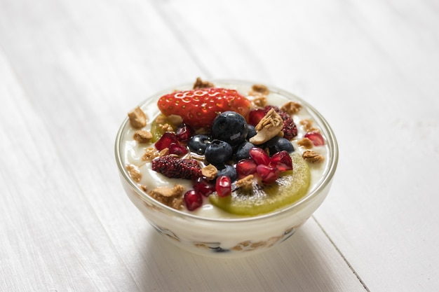 Plain yogurt with strawberry, blueberries, kiwi, granola, pomegranate in a glass bowl and honey